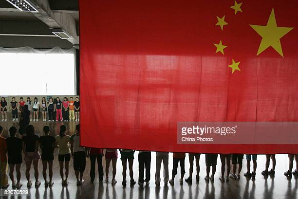 Members of a cheering squad take part in training below China's national flag on July 25, 2008 in Yanjiao of Hebei Province, China. A total of 27...