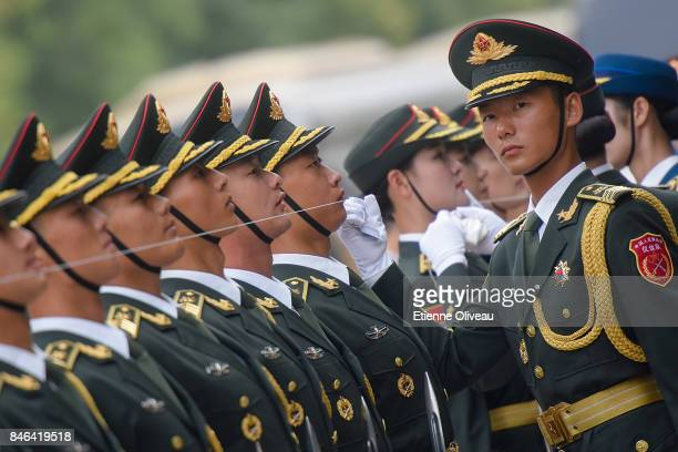 Members of a Chinese military honour guard prepare before a welcome ceremony for Sultan of Brunei Hassanal Bolkiah outside The Great Hall Of The...