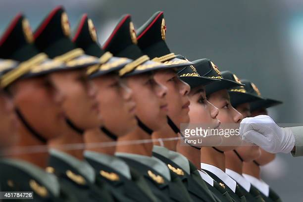 Members of a Chinese People's Liberation Army honour guard line up behind a string which is used to make sure that they are standing in a straight...