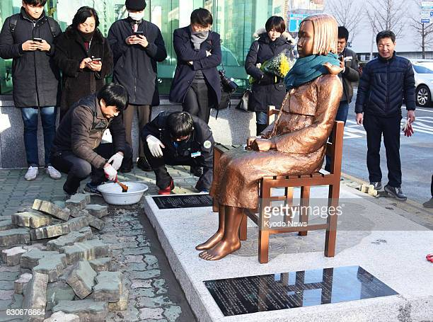 Members of a civic group install a statue symbolizing women forced into wartime Japanese military brothels in front of the Japanese Consulate in the...