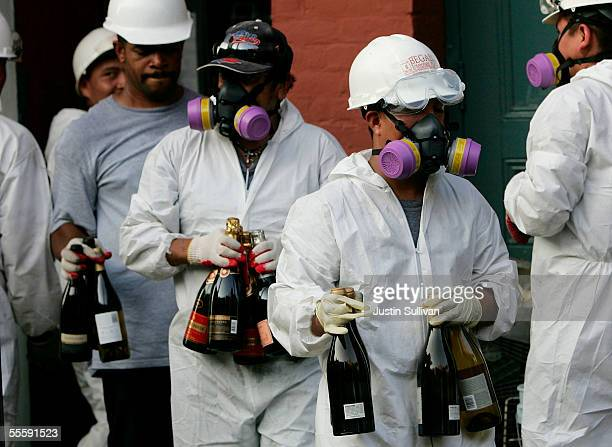 Members of a cleanup crew wear protective gear as they remove contaminated bottles of wine champagne and food from a restaurant in the French Quarter...