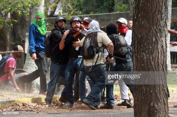 Members of a colectivo pro government group attack El Nacional opposition newspaper photographer Leonardo Rodriguez who was covering a protest of...