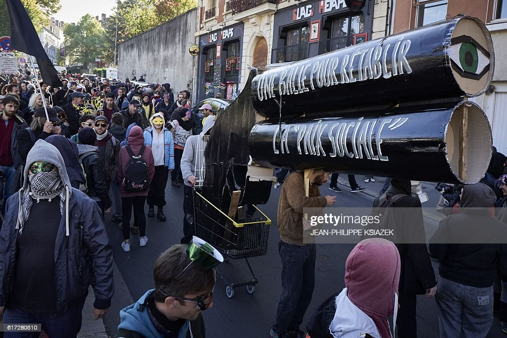 Members of a collective for 'the disarmament of police and the demilitarisation of conflicts' stand near a giant mock gun with a message reading 'A bullet to restore social peace' as they demonstrate on October 22, 2016 in Saint-Etienne. Around 300 people took part in the demonstration today despite a ban from the prefecture. / AFP / JEAN