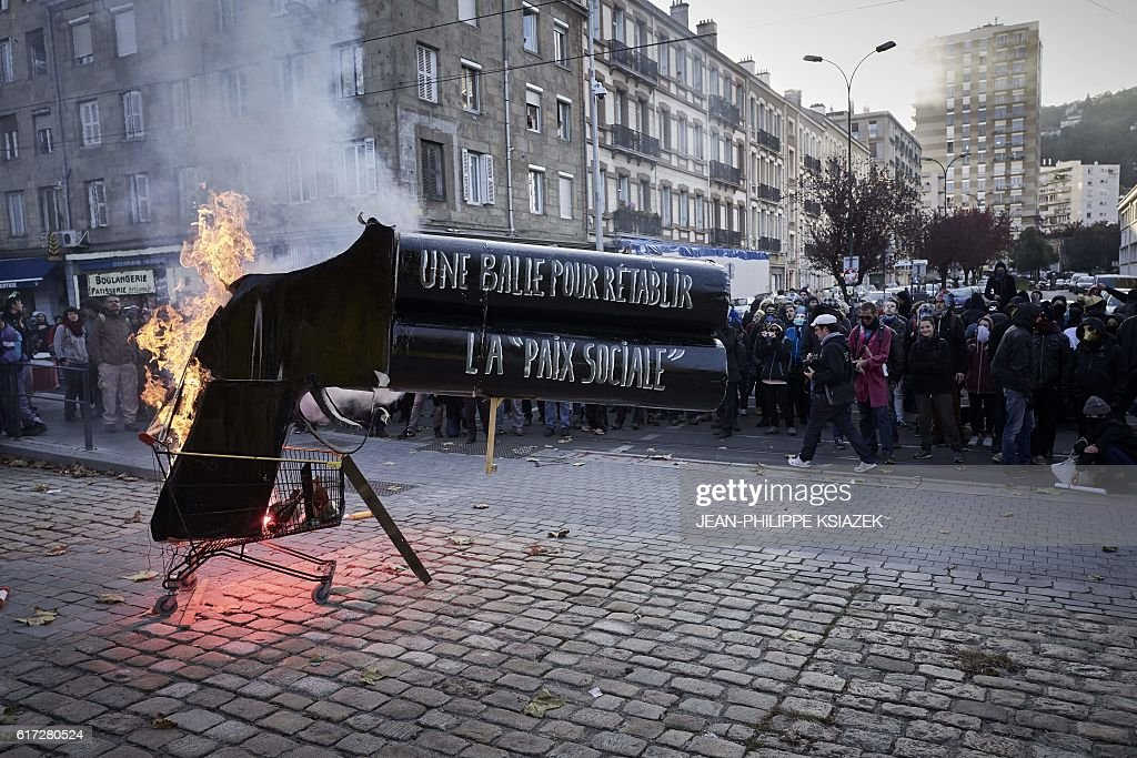 TOPSHOT - Members of a collective for 'the disarmament of police and the demilitarisation of conflicts' stand near a giant mock gun with a message reading 'A bullet to restore social peace' as they demonstrate on October 22, 2016 in Saint-Etienne. Around 300 people took part in the demonstration today despite a ban from the prefecture. / AFP / JEAN