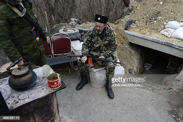 Members of a Cossack unit aligned with the selfproclaimed Luhansk People's Republic man a checkpoint near a bridge over the river Donets in Stanytsia...