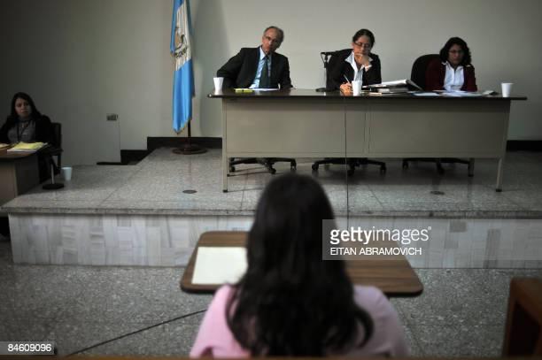 Members of a court listen to Vilma Angelica de La Cruz Marroquin in Guatemala City on February 3 as she testifies against her husband Calixto Simon...
