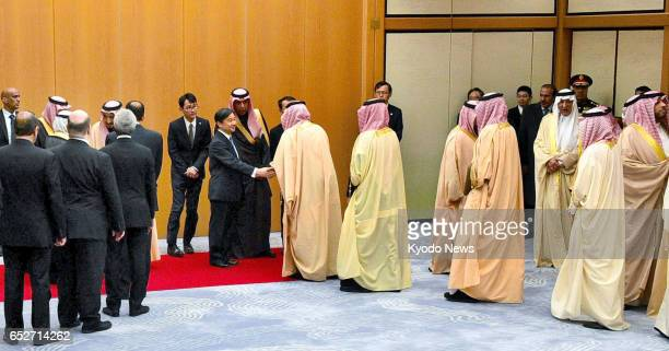 Members of a delegation accompanying King Salman bin Abdulaziz of Saudi Arabia shake hands with Japanese Crown Prince Naruhito at Tokyo's Haneda...
