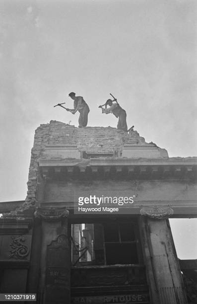 Members of a demolition crew at work on a site near the offices of Picture Post magazine in Shoe Lane, off Fleet Street, London, September 1941....