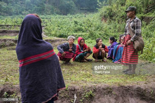 Members of a displaced people family gather in a ricefield.