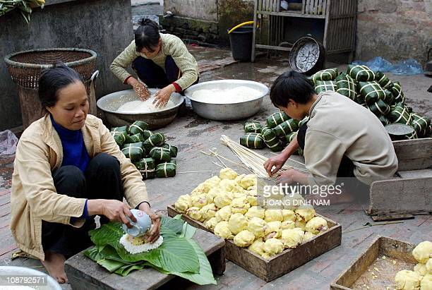 Members of a family are busy making the traditional lunar new year 'banh chung' or rice cakes for sale on the courtyard of their house in Chanh Khuc...