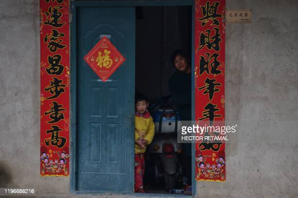 Members of a family are seen in their house in a neighborhood on the outskirts of Wuhan in China's central Hubei province on January 27 amid a deadly...