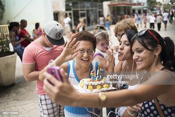 Members of a family bring a birthday cake to a public square with Wifi connectivity to the internet to celebrate the 15th birthday of one of their...
