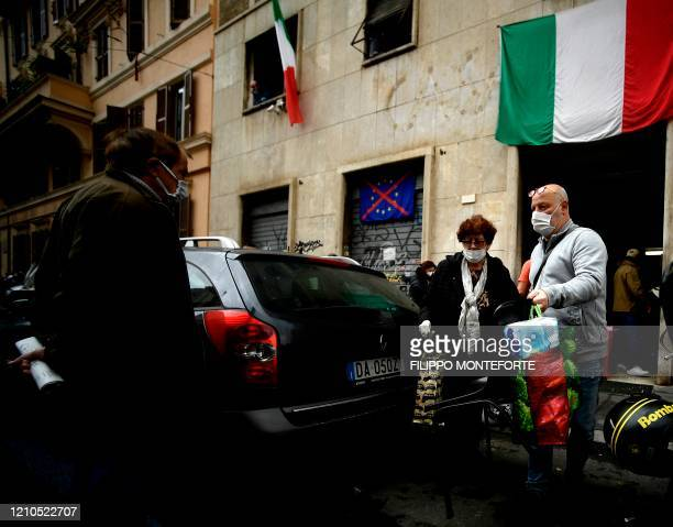 Members of a family carry shopping bags handed for free by activists of Italian neo-fascist movement Casapound on April 21, 2020 in Rome, during the...