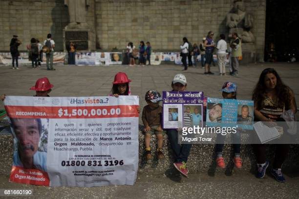 Members of a family hold signs with images of there missing relatives during a march on Mother's Day on May 10 2017 in Mexico City Mexico Mothers...