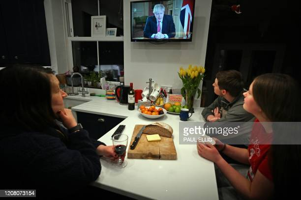 Members of a family listen as Britain's Prime Minister Boris Johnson makes a televised address to the nation from inside 10 Downing Street in London...
