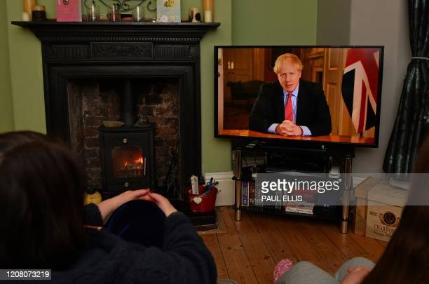 TOPSHOT Members of a family listen as Britain's Prime Minister Boris Johnson makes a televised address to the nation from inside 10 Downing Street in...