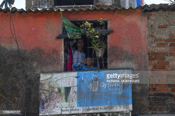 Members of a family peer out of a window of their tenement at the Dharavi slum during a governmentimposed nationwide lockdown as a preventive measure...