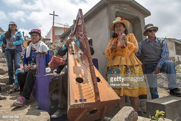 Members of a family pose for a picture next to z tomb during the Day of the Dead celebrations at Nueva Esperanza cemetery on November 0 2016 in Lima...