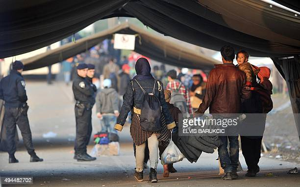 Members of a family walk towards Croatian policemen as migrants and refugees cross the SerbianCroatian border in the village of Berkasovo near the...