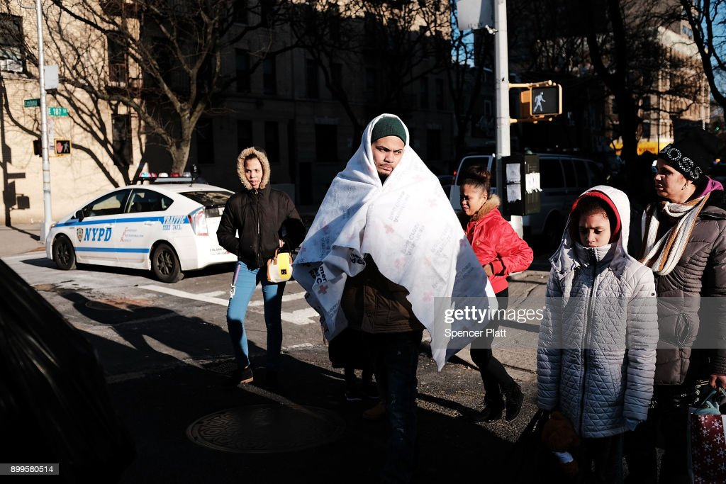 Members of a family who had to evacuate their apartment following a deadly fire walk near the scene the day after in the Bronx on December 29, 2017 in New York City. At least 12 people, including at least four children were killed in the blaze which officials believe was started by a child playing with the stove.