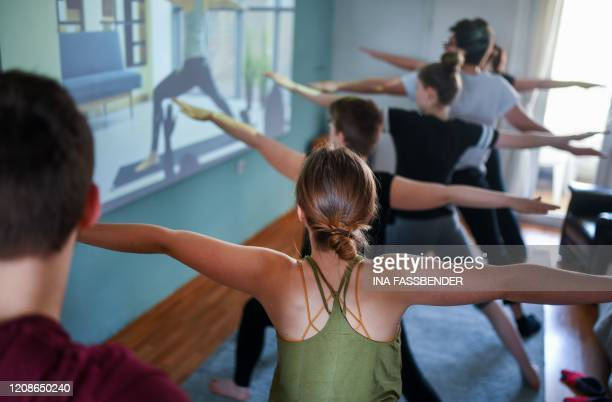 Members of a flatsharing take part in a yoga session with a beamer in their living room in Dortmund western Germany on March 27 amidst the pandemic...