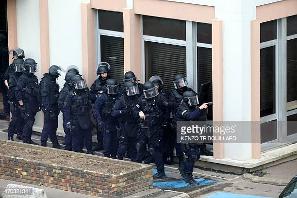 Members of a French police intervention squad advance in formation at the bottom of a building where four suspected armed robbers have taken refuge...
