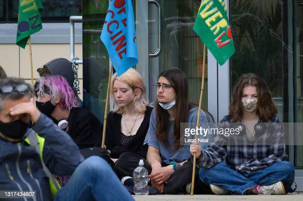 """Members of a group called """"The People's Vaccine"""" hold a minute's silence during a protest outside the AstraZeneca headquarters as they call for the..."""