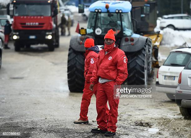 Members of a group of migrants who volunteer with the Italian Red Crosss prepare the Penna operating center, some 20 km from the site of an avalanche...