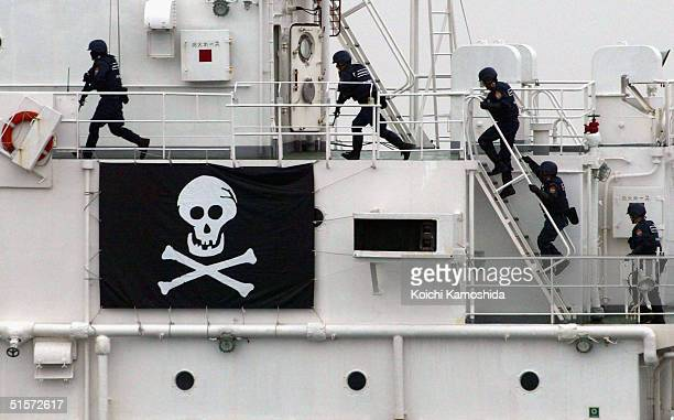Members of a Japanese antiterrorist unit board a ship during a drill in a multilateral naval exercise on Sagami Bay at sea October 26 in Sagami Bay...