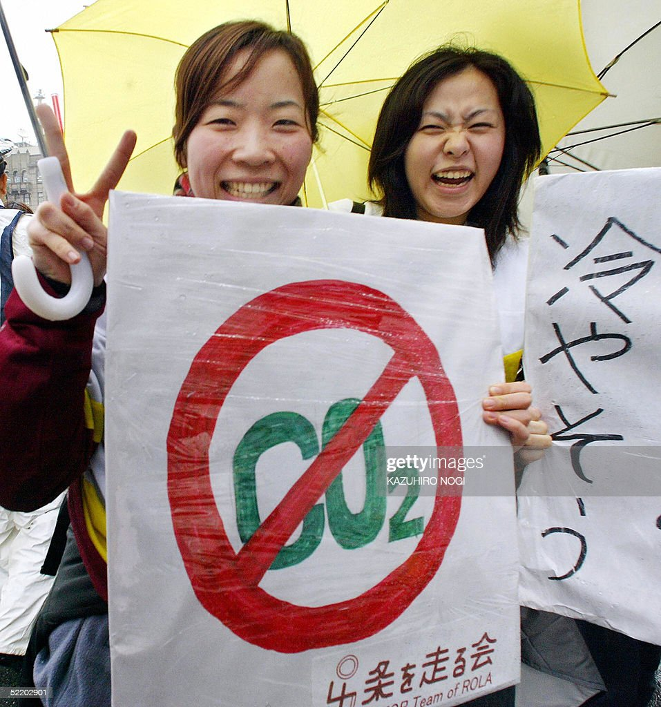 Members of a Japanese environmental group smile while holding anti-carbon dioxide placards during a demonstration in downtown Kyoto, 16 February 2005, to celebrate the Kyoto Protocol, the world's most far-reaching environmental treaty. The treaty took effect at midnight at UN headquarters in New York (0500 GMT), which was 2:00 pm in Kyoto, the ancient Japanese city where the landmark agreement now supported by 141 countries was reached in 1997. AFP PHOTO/Kazuhiro NOGI