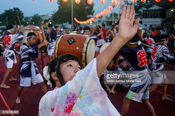 Members of a Japanese living in Malaysia wearing a traditional yukatas perform a dance during the 40th Bon Odori festival on July 23 2016 in Shah...