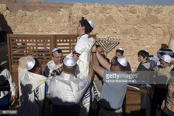 Members of a Jewish family lift a boy as they dance during his Bar Mitzvah ceremony in the ancient synagogue of the hilltop fortress of Masada in the...
