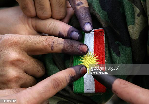 Members of a Kurdish Peshmerga battalion show their inkstained fingers in front of an insignia after voting in the region's legislative elections at...