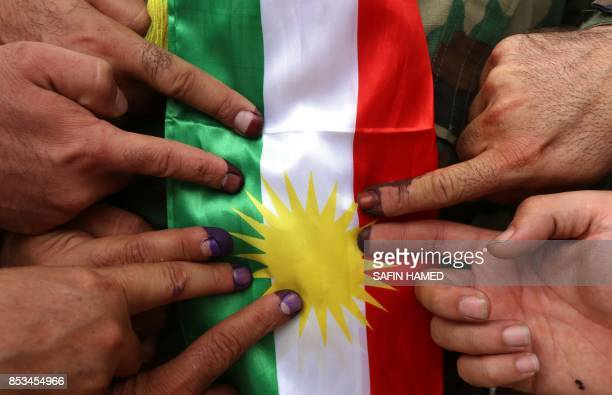 Members of a Kurdish Peshmerga battalion show their inkstained fingers in front of a Kurdish flag after voting in the Kurdish independence referendum...