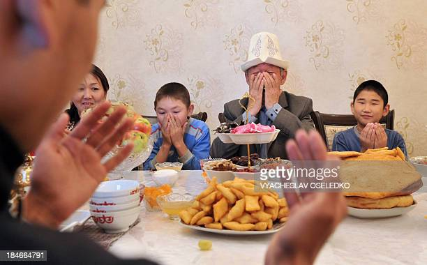 Members of a Kyrgyz family pray around a festive meal on the first day of the Eid alAdha in the village of KokZhar on the outskirts of Bishkek on...