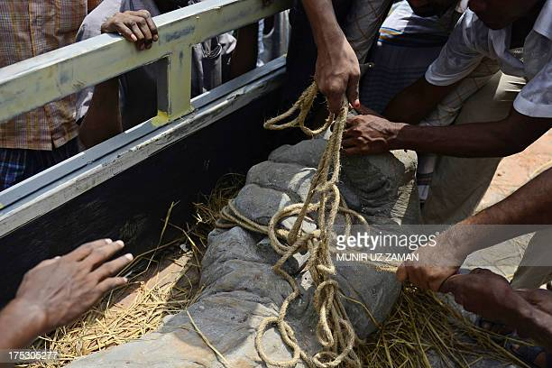 Members of a labour organisation unload a sculpture, representing a worker's upheld fist, as a monument to mark the April 24 Rana Plaza garment...
