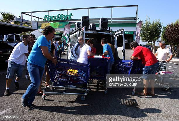 Members of a leftwing group Sindicato Andaluz de Trabajadores unload into waiting vehicles shoping trolleys full of school supplies taken from a...