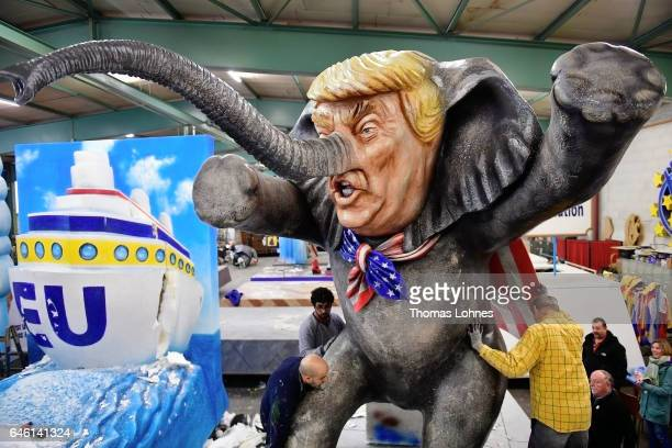 Members of a local carnival association take apart a float showing US President Donald Trump the day after the annual Rose Monday parades on February...