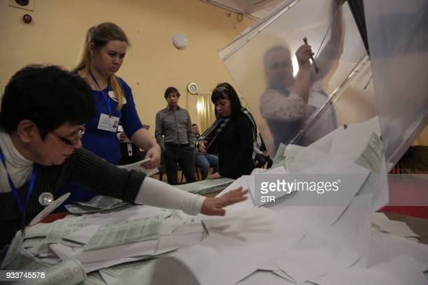 Members of a local election commission empty a ballot box as they start counting votes during Russia's presidential election in Simferopol Crimea on...