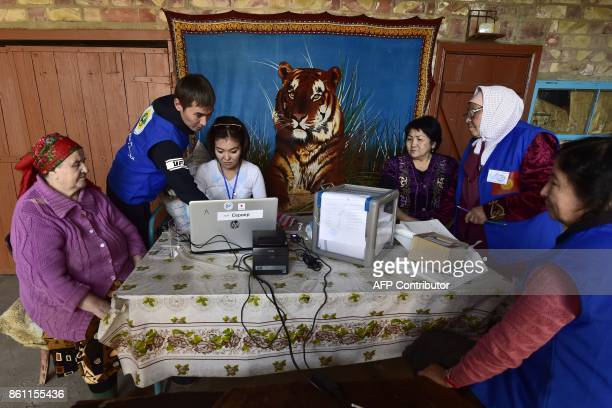 Members of a local election commission perform the electronic identification of a voter at a home during an early voting in the presidential election...