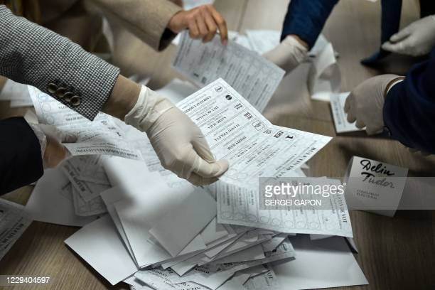Members of a local electoral commission wearing face masks and gloves count votes in Moldova's presidential election at a polling station in Chisinau...