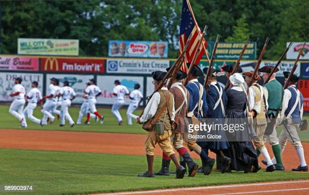 Members of a local militia group march in line onto the field for pregame ceremonies while at the same time in the outfield members of the Spinners...