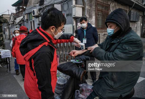Members of a local neighbourhood committee wear protective masks as they check the temperature of a resident entering at a barricade placed to...