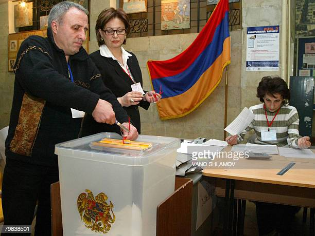 Members of a local voting commission remove the seals at a ballot box to begin their vote count in Armenian presidential elections at a polling...