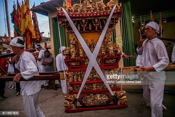 Members of a Malaysian ethnic Chinese community carrying the shrine of the emperor god on sedan chair circle around the pit during the Nine Emperor...