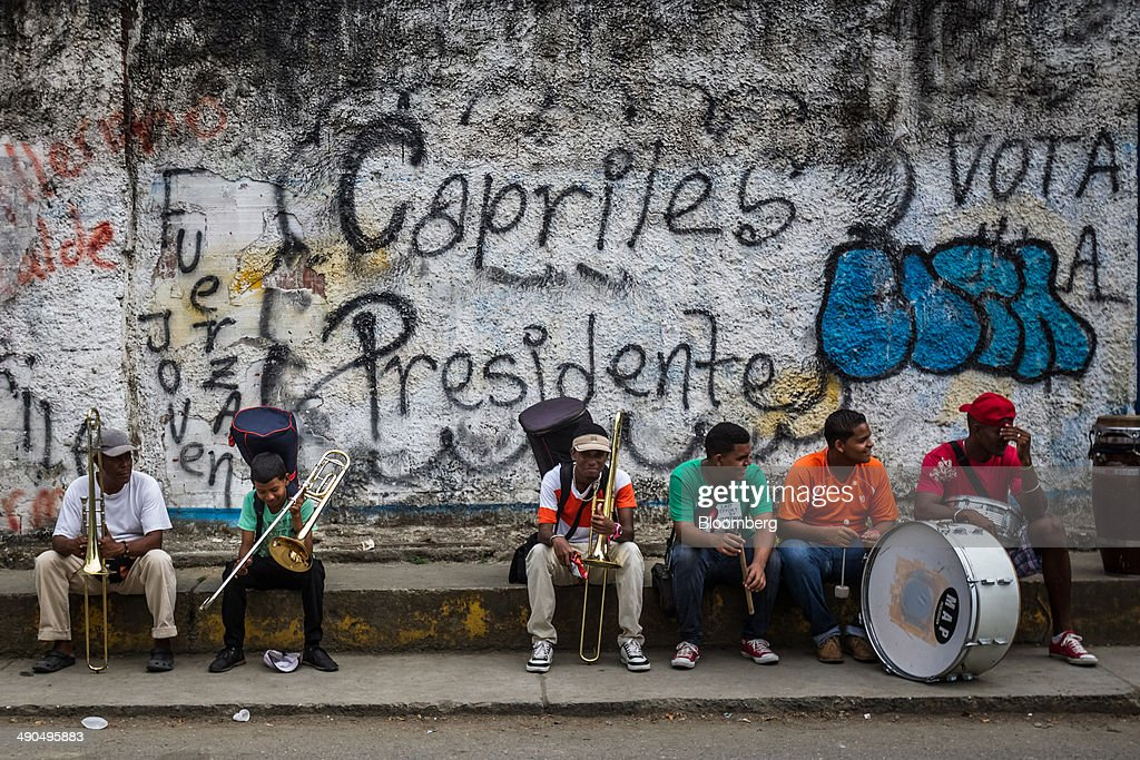 Members of a marching band sit under graffiti urging people to vote for Henrique Capriles, governor of the state of Miranda and a former presidential candidate in the last two elections, during a visit by Capriles in Barlovento, Venezuela, on Saturday, May 10, 2014. Capriles, one of the leaders of the Democratic Unity Roundtable, known as MUD, an alliance which opposes Venezuelan President Nicolas Maduro, said talks with the government scheduled for May 8 were canceled because they 'haven't produced any result up to now.' Photographer: Meridith Kohut/Bloomberg via Getty Images