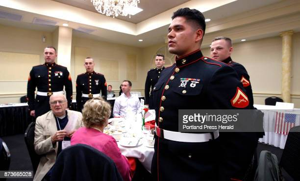 Members of a Marine Corps honor guard based in Brunswick rise to their feet along with other Marines to sing 'The Marines' Hymn' during an armed...