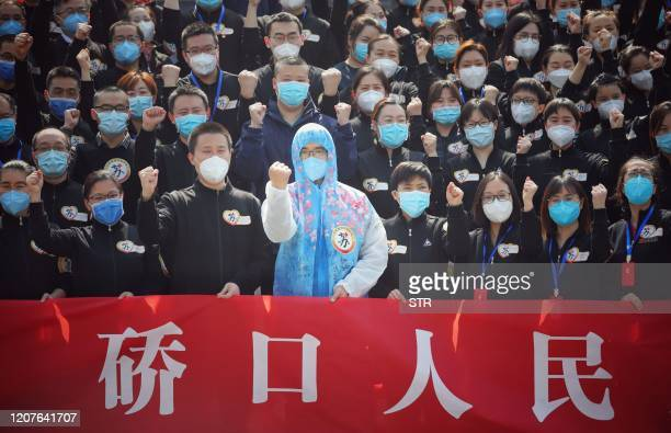 Members of a medical assistance team from Jiangsu province chant slogans at a ceremony marking their departure after helping with the COVID-19...