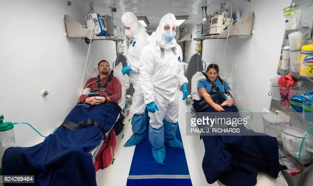 Members of a medical team monitor simulated patients infected with Ebola inside a Containerized BioContainment System during a shakedown exercise at...