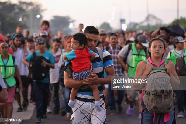 Members of a migrant caravan walk into the interior of Mexico after crossing the Guatemalan border on October 21 2018 near Ciudad Hidalgo Mexico The...